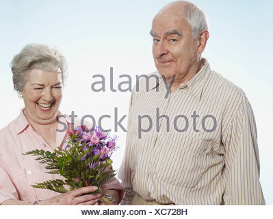 Senior man knows she's happy when he gives her flowers - Stock Photo