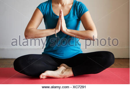 Cropped view of woman sitting cross legged, hands together meditating - Stock Photo