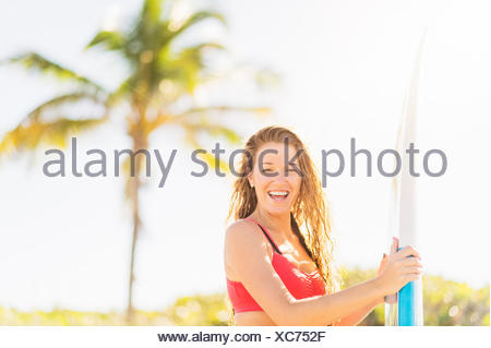 USA, Florida, Jupiter, Portrait of young woman holding surfboard on beach - Stock Photo