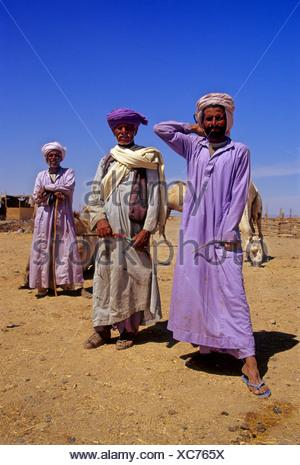 Three Bedouins in traditional dress, pride, Egyptian, djellaba, turban, pose, Camel market, Shalatin, Egypt, Africa - Stock Photo