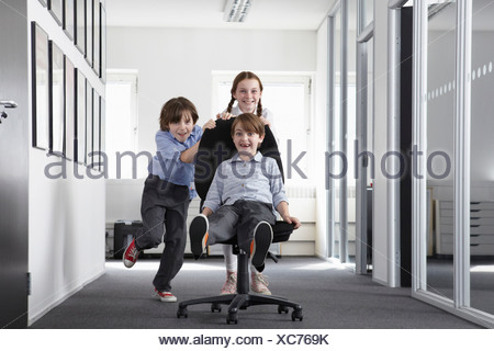Three children playing in office corridor on office chair - Stock Photo