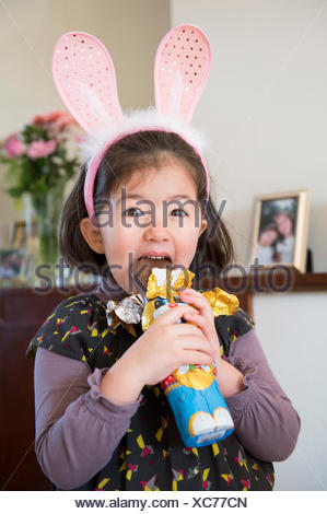 Young girl wearing bunny ears, just about to bite into chocolate bunny - Stock Photo