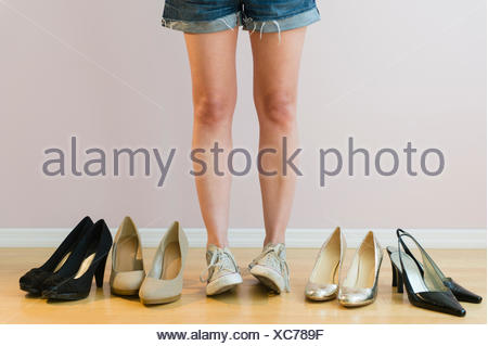 Studio shot of woman with pairs of shoes - Stock Photo