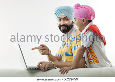 Father showing something on his laptop to his son - Stock Photo