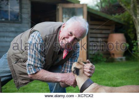 Senior man, stroking pet dog in garden - Stock Photo