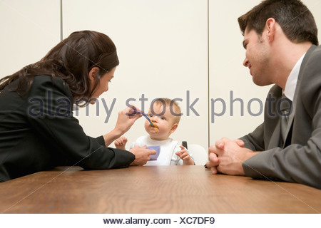 Parents feeding their baby in board room - Stock Photo