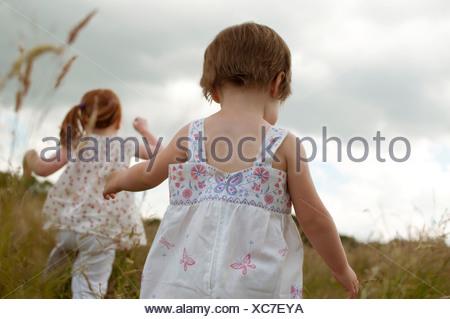 Two little girls walking in a field, rear view - Stock Photo
