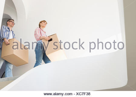 Low angle view of couple with boxes moving into new house - Stock Photo