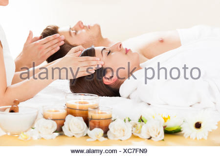 Young couple receiving head massage at beauty spa - Stock Photo