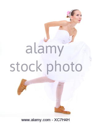 Wedding day. Running bride funny young woman wearing sporting shoes isolated on white background - Stock Photo