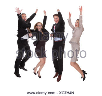 Four diverse professional business partners jumping for joy with their arms raised shouting in jubilation isolated on white - Stock Photo