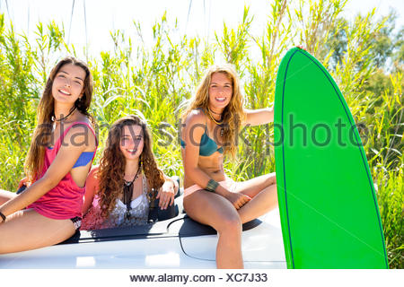 surfer beautiful girls group holding happy surfboards on convertible car. - Stock Photo
