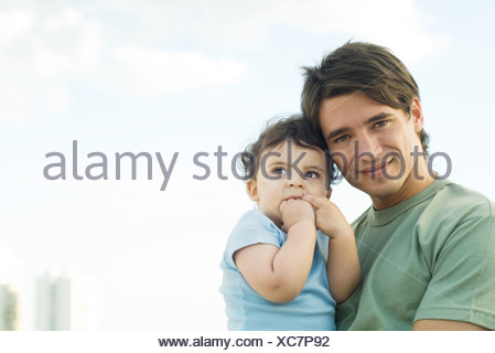 Father holding baby, smiling at camera - Stock Photo