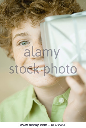 Boy holding up present in front of face - Stock Photo