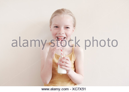 Young girl drinking milk from straw, portrait - Stock Photo