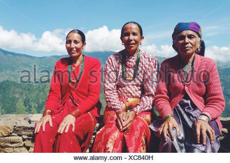 Portrait of three local Nepalese women sitting on a wall in a mountain village, Nepal - Stock Photo