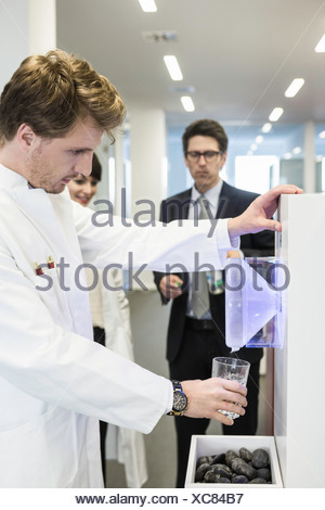 Man wearing lab coat getting drink from water cooler - Stock Photo