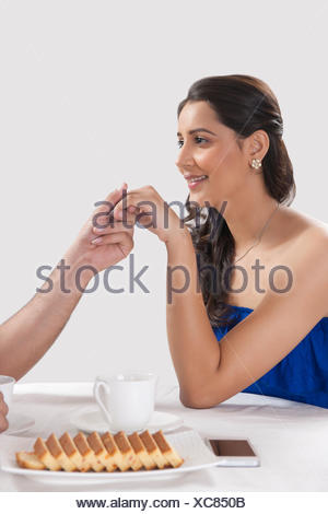 Cropped image of man holding woman's hand while having coffee against white background - Stock Photo