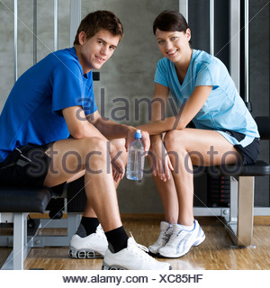 Two friends sitting in a gym - Stock Photo