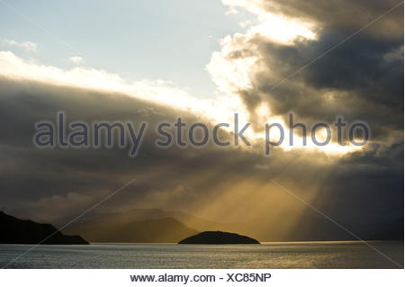 Sunrays break through a thick cloud cover over the sea and illuminated a small island and in the background fjords at the north end of the south island of New Zealand. - Stock Photo