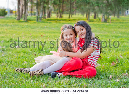 Two girls sitting in the park, hugging - Stock Photo