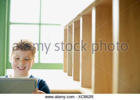 Redheaded boy on computer in classroom. - Stock Photo