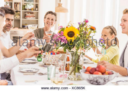 Family making champagne toast at birthday party table - Stock Photo