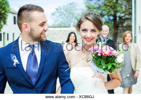 Bride and groom walking with family in background - Stock Photo