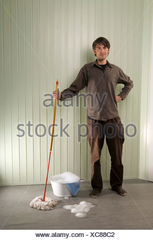 A man standing with a mop and bucket - Stock Photo