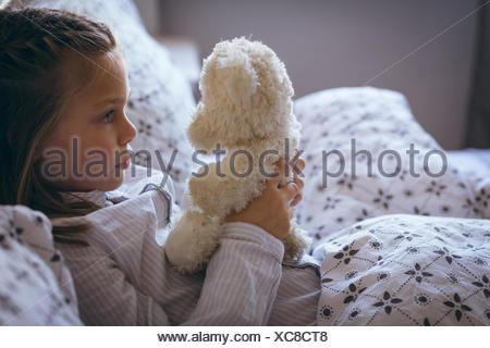Girl holding teddy bear on bed - Stock Photo