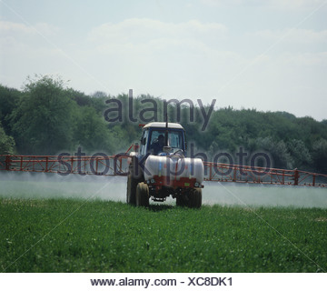 Ford tractor with 24 metre Lely boom sprayer and front mounted tank spraying young barley crop - Stock Photo