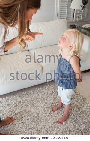 A scolded child looks up to her mother as she is being punished - Stock Photo