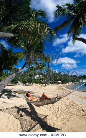 Woman in a hammock on Bolongo Beach, St. Thomas Island, United States Virgin Islands, Caribbean - Stock Photo
