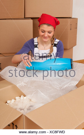 young woman new home unpacking moving in boxes - Stock Photo