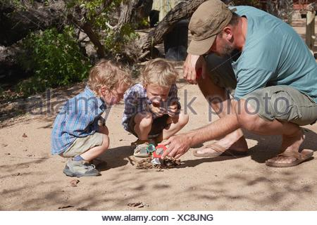 Father and sons trying to start camp fire using magnifying glass and sun, Purros, Kaokoland, Namibia - Stock Photo