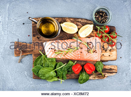 Ingredients for cooking healthy dinner. Raw salmon fillet, spinach, tomatoes, olive oil, lemon, peppers, rosemary and spices on - Stock Photo