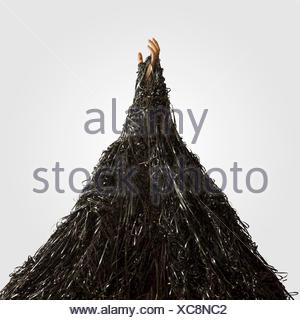 Man's hand emerging from pile of recording tape - Stock Photo
