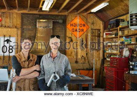 Portrait of welder and designer in workshop - Stock Photo