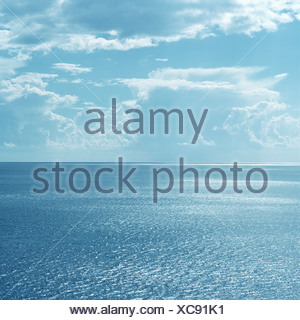 Clouds over still ocean waters - Stock Photo