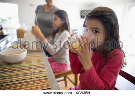 Portrait smiling girl drinking orange juice at breakfast bar in kitchen - Stock Photo
