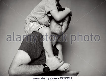 Boy sitting on his father's shoulders - Stock Photo