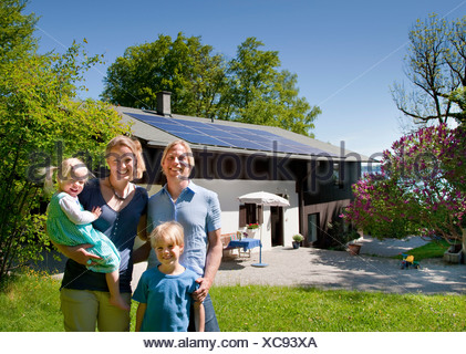 Family at home with solar panel - Stock Photo