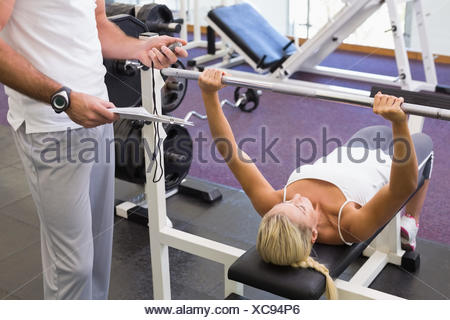 Trainer with clipboard besides woman lifting barbell in gym - Stock Photo