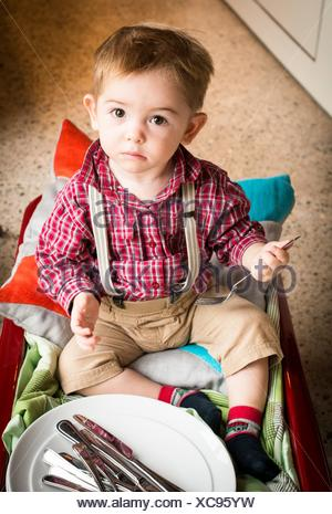 baby boy, 18 months old, helps with the dishes. - Stock Photo