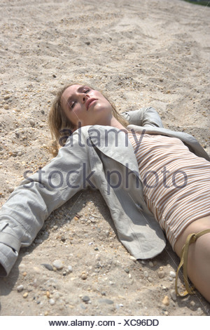Female lying on a beach wearing a yellow and white striped top, gold bikini bottoms and a grey jacket  Frowein - Stock Photo