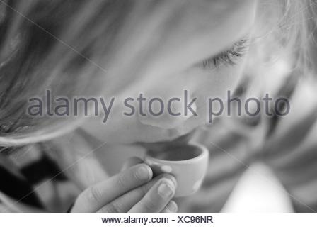 Argentina, Buenos Aires, Little girl drinking tea - Stock Photo