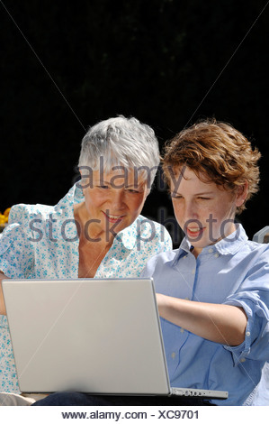 Grandson is showing his grandmother something on a laptop computer - Stock Photo