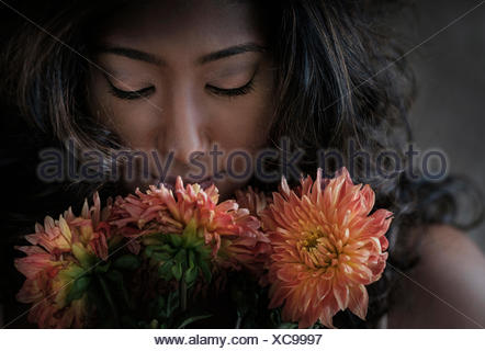 Young woman smelling flowers - Stock Photo