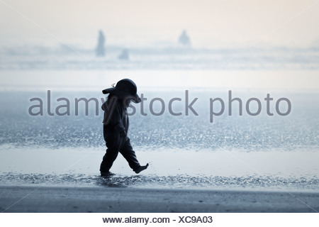 Young Girl Walking In The Fog On Long Beach In Pacific Rim National Park; Vancouver Island British Columbia Canada - Stock Photo