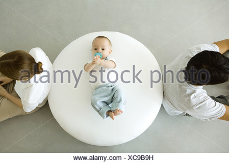 Infant lying on ottoman, mother and father sitting with backs turned, overhead view - Stock Photo